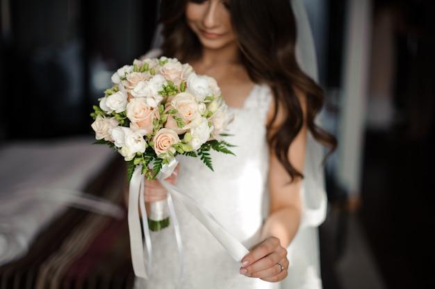 花嫁の朝の準備。白いドレスとベールのウェディングブーケに身を包んだ美しい花嫁 Premium写真