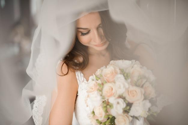 Невеста утренняя подготовка. милая невеста в белой вуалью со свадебным букетом Premium Фотографии
