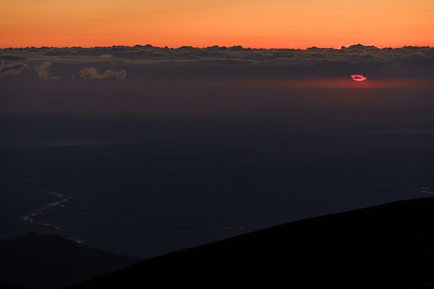 雲と澄んだオレンジ色の夕焼け空に緑の草に覆われた丘からの風景 Premium写真