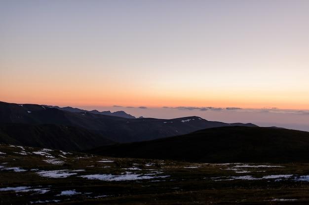 日没の曇り空を背景に草や雪の残骸で覆われた丘の風景 Premium写真