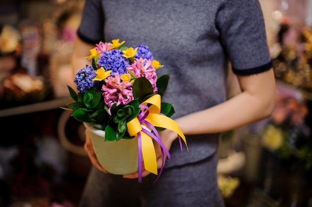 カラフルなヒヤシンスと白い植木鉢を保持している女性 Premium写真