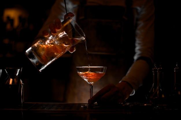 暗闇の中で計量カップからグラスに茶色のアルコールカクテルを注ぐ男性バーテンダー Premium写真