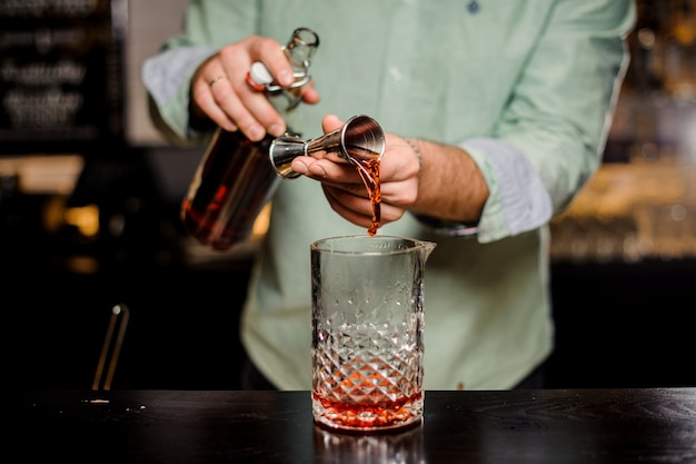 Бармен делает алкогольный коктейль, металлический джиггер и барную среду Premium Фотографии