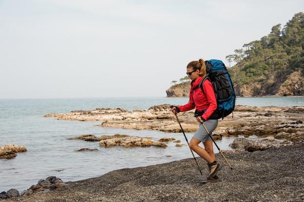 海岸でのハイキングのサングラスの女性 Premium写真