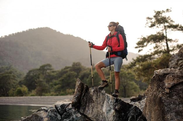 ハイキング用具を持つ女性が石の多い海岸を歩く Premium写真
