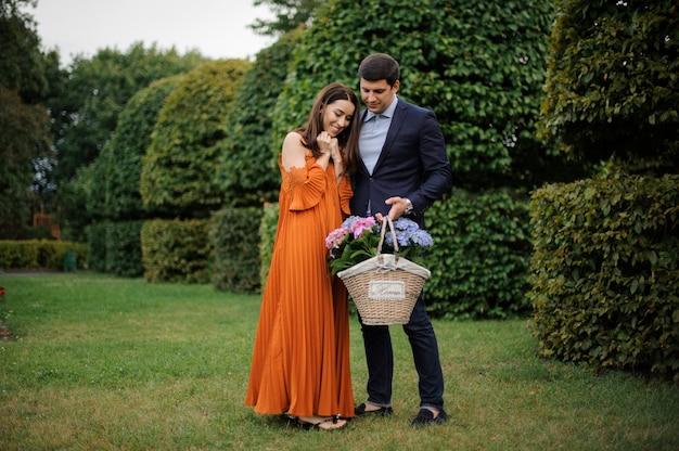 Красивая и стильная пара с большой плетеной корзиной, полной цветов Premium Фотографии