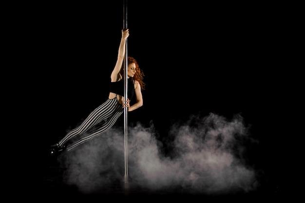 ポールダンスを実行する素敵な赤髪の女性 Premium写真