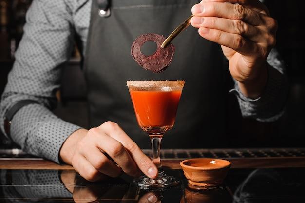 塩とビートと赤いアルコール飲料で満たされたカクテルグラスを飾るバーテンダー Premium写真