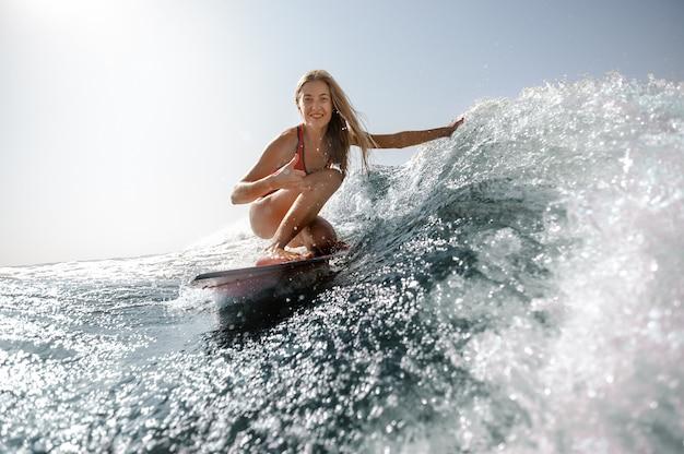 水着サーフィンの女性のショットを閉じる Premium写真