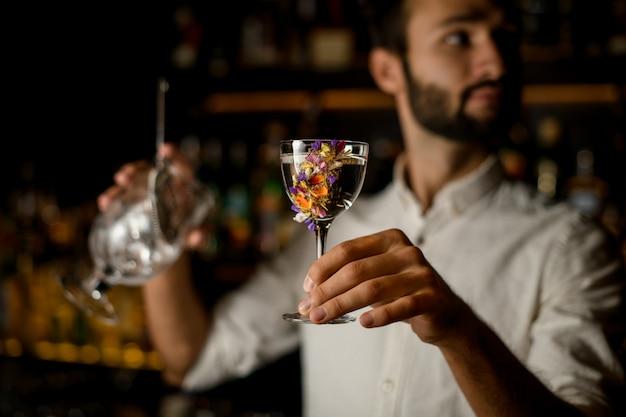 Бармен с бородой держит в стакане спирт и ситечко Premium Фотографии