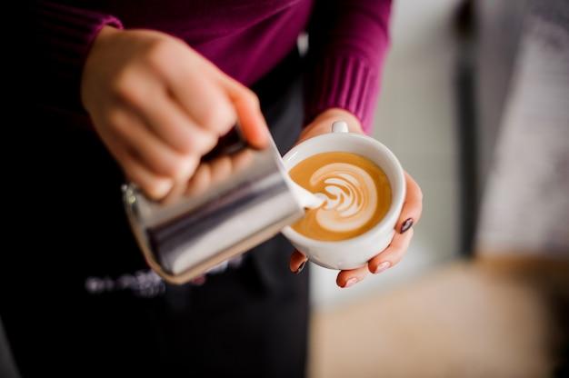 コーヒーショップでコーヒーカフェラテアートを作るバリスタ Premium写真