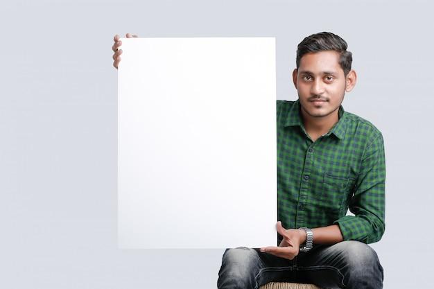 白い背景の上に空白の歌うボードを示す若いインド人 Premium写真