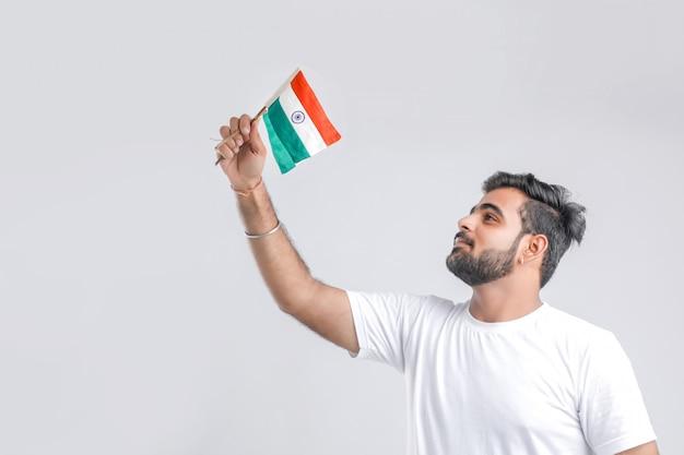 Молодой индийский студент колледжа смотря индийский флаг. Premium Фотографии