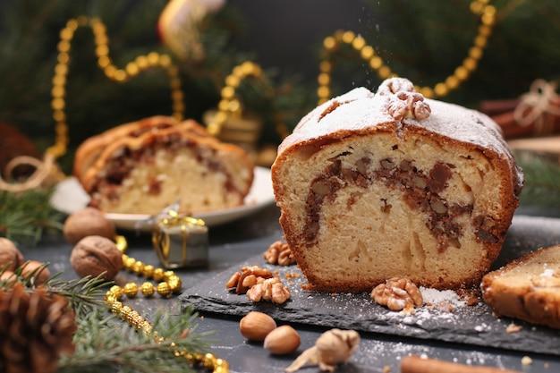 ナッツと砂糖漬けのクリスマスカップケーキ、クリスマスにある粉砂糖で覆われています。 Premium写真