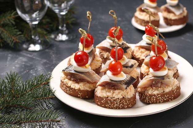 Канапе с соленой сельдью, сыром, перепелиными яйцами и помидорами черри на ржаных гренках Premium Фотографии