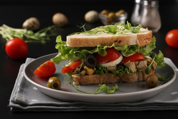 Бутерброд с курицей, помидорами черри, перепелиными яйцами, маслинами и зеленью на темном столе Premium Фотографии
