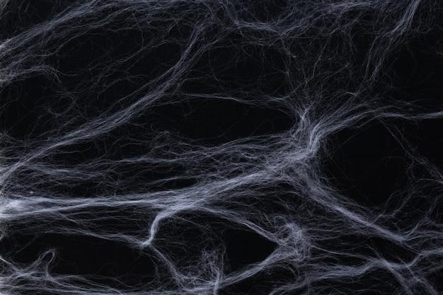 ハロウィーンのコンセプト。黒の背景に抽象的なクモの巣。 Premium写真