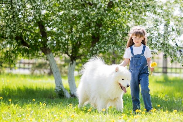 Маленькая девочка с большой белой собакой в парке. Premium Фотографии