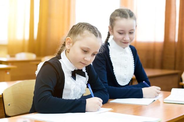 Девочка одноклассника заглядывает в чужую тетрадь. Premium Фотографии