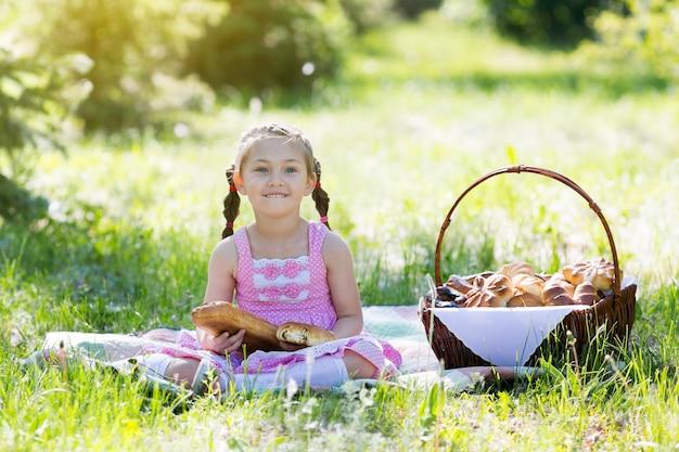 子供が草の上に座ってパンを食べています。 Premium写真