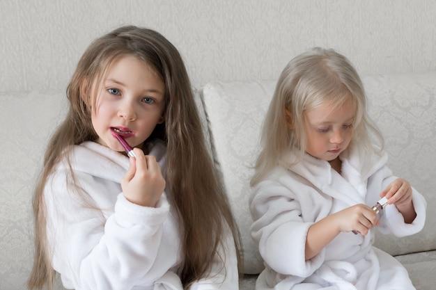 Подружки девушек красят губы помадой. Premium Фотографии