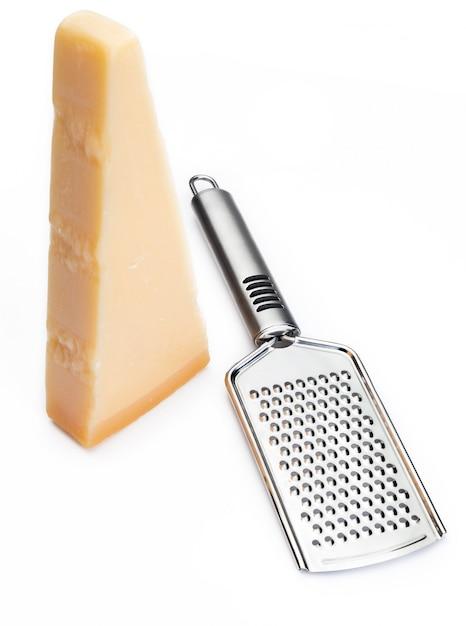 おろし金とパルメザンチーズまたはグラナのくさび。 Premium写真