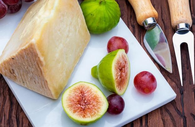 Инжир, красный виноград и овечий сыр (типа манчего). на белом мраморе и дереве. Premium Фотографии