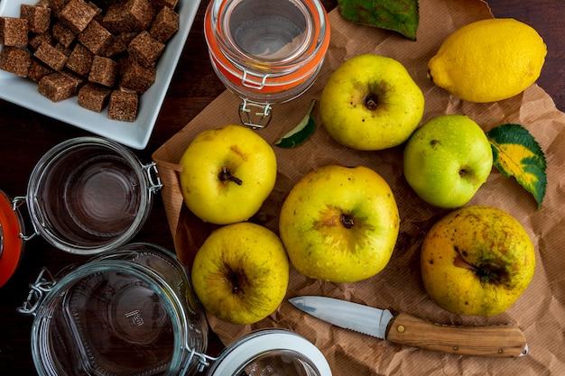 Ингредиенты для приготовления варенья и яблочного пюре (желтый, реинетас). с сахаром, лимоном и стеклянными банками. Premium Фотографии