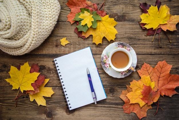 黄色の葉、お茶、スカーフ、木製の背景にペンで紙切れの秋の写真 Premium写真