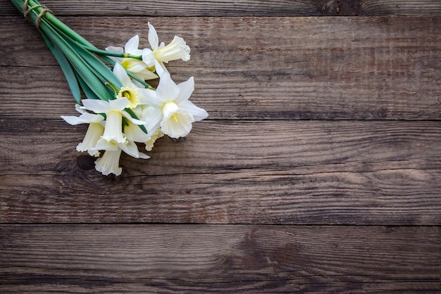木製のテーブルに黄色い水仙と白の花束 Premium写真
