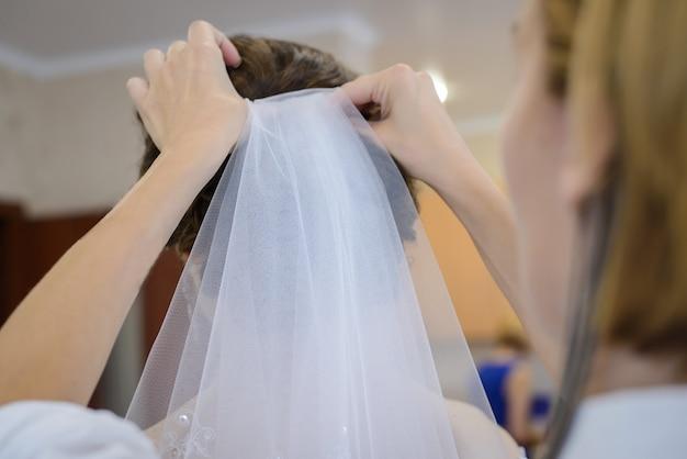 Парикмахер прикрепляет вуаль к свадебной прическе невесты Premium Фотографии
