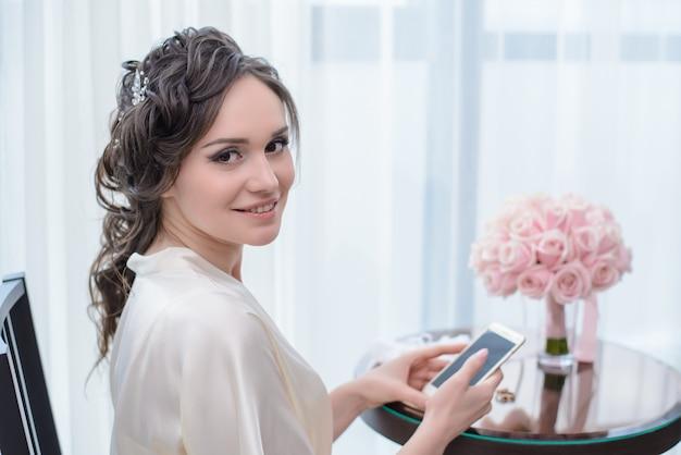 電話で窓際に座っている朝の花嫁 Premium写真
