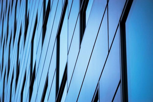 オフィスビルの窓の背景。オフィスビルのガラスのファサード Premium写真