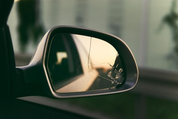 後ろを見ると車のサイドミラー。壊れたミラーをクローズアップ。 Premium写真