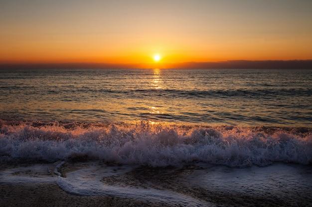 海の波とビーチで夕日と夕方 Premium写真