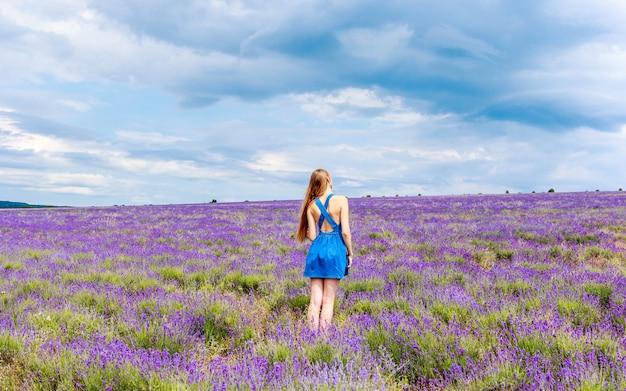曇りの天候でラベンダー畑の青いドレスの女性。 Premium写真