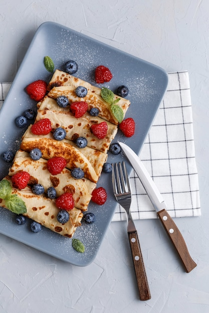 ミントで飾られたラズベリーとブルーベリーのツイスト薄いパンケーキ Premium写真