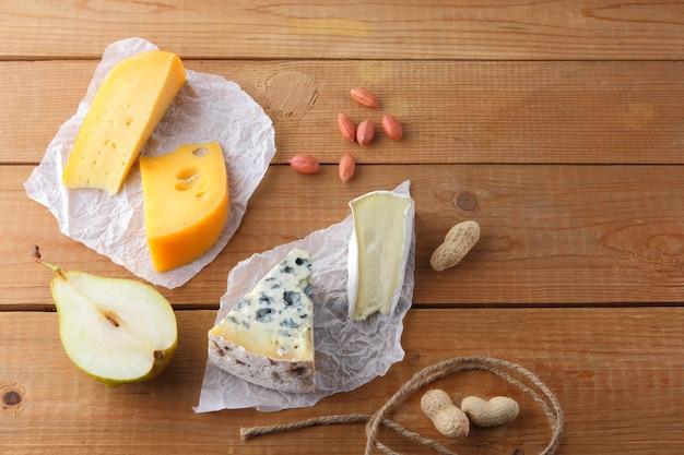 羊皮紙にチーズ、梨、ピーナッツの品揃え。カマンベール、硬い黄色のチーズ、木の板にドルブル。乳製品、半梨、ナッツ Premium写真