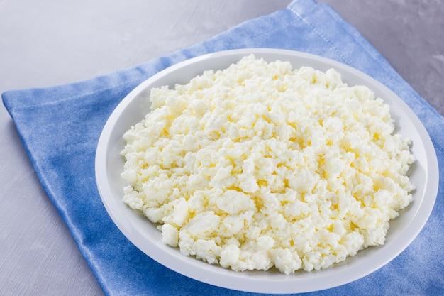 プレートのカッテージチーズ。白いプレートに新鮮なカッテージチーズ。青いナプキンに柔らかいチーズ Premium写真