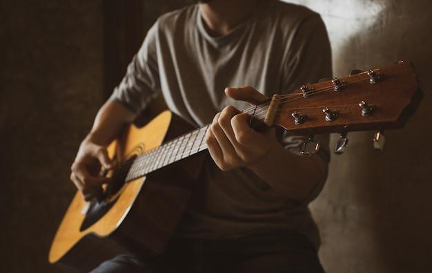 部屋の隅でピッキングアコースティックギターソロ指スタイルを演奏するアジアの男性ミュージシャン。 Premium写真