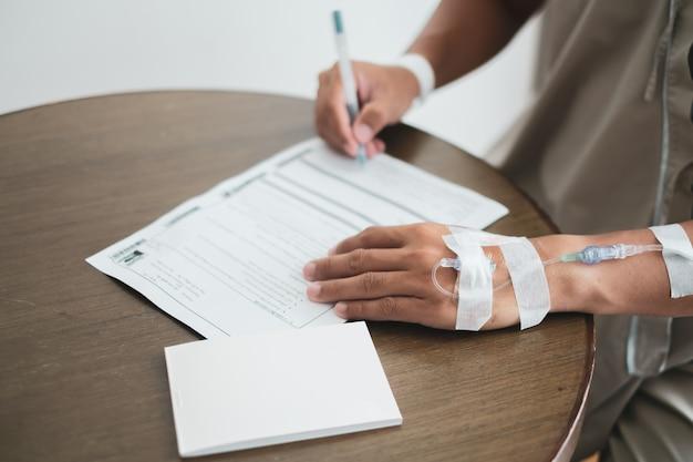 男性患者の医療請求書に署名し、病院で働く書類を保険します。 Premium写真