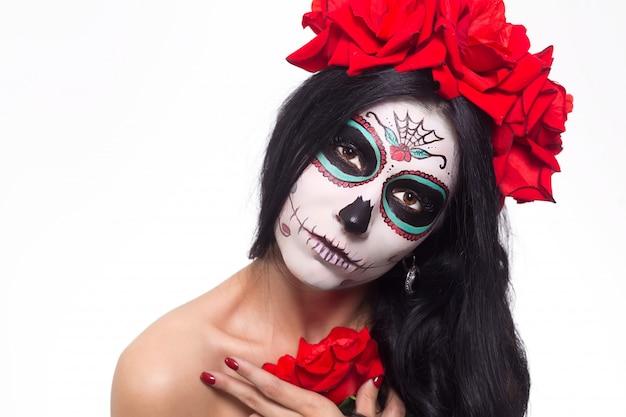死霊のえじき。ハロウィン。死んだマスク頭蓋骨顔アートとバラの日の若い女性。白で隔離。閉じる。 Premium写真
