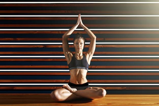 Молодая женщина делает упражнения йоги в темной студии. концепция здорового образа жизни. Premium Фотографии