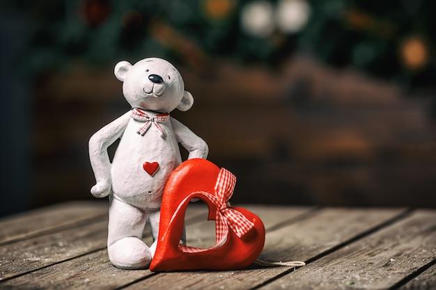 Кукла белого медведя при сердце стоя на старой деревянной предпосылке. валентина концепция Premium Фотографии