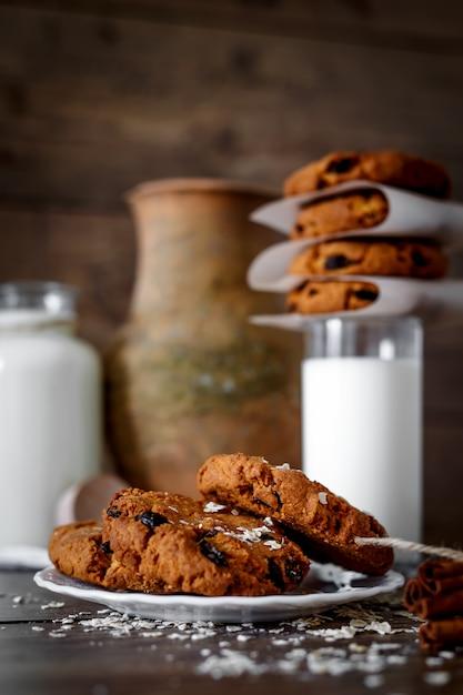 暗い背景の木にミルクとナッツのレーズンとガラスの自家製オートミールクッキー Premium写真