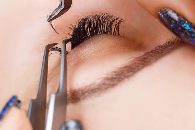 Процедура наращивания ресниц. женский глаз с длинными ресницами Premium Фотографии