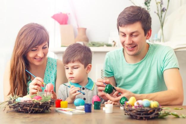 Мать, отец и сын красят яйца. счастливая семья готовится к пасхе. Premium Фотографии