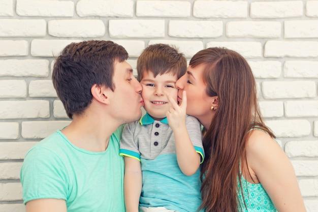 レンガ壁の背景に幸せと笑顔の若い家族の肖像画。父と母と小さな男の子。子供を持つ親 Premium写真
