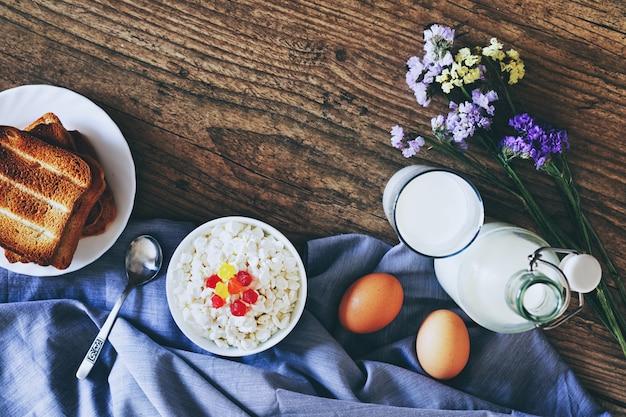 Молочные продукты на темном деревянном столе. сметана, молоко, сыр, яйцо и тосты. вид сверху с копией пространства Premium Фотографии