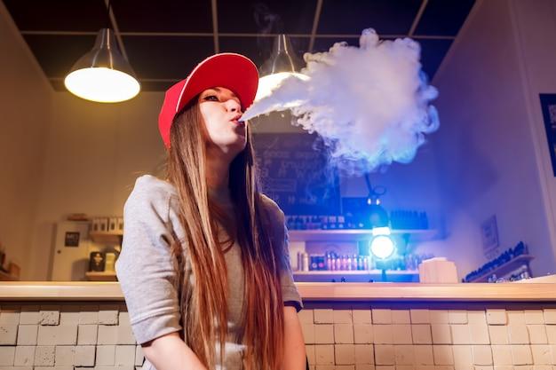 赤い帽子の若いきれいな女性がアークショップで電子タバコを吸う Premium写真